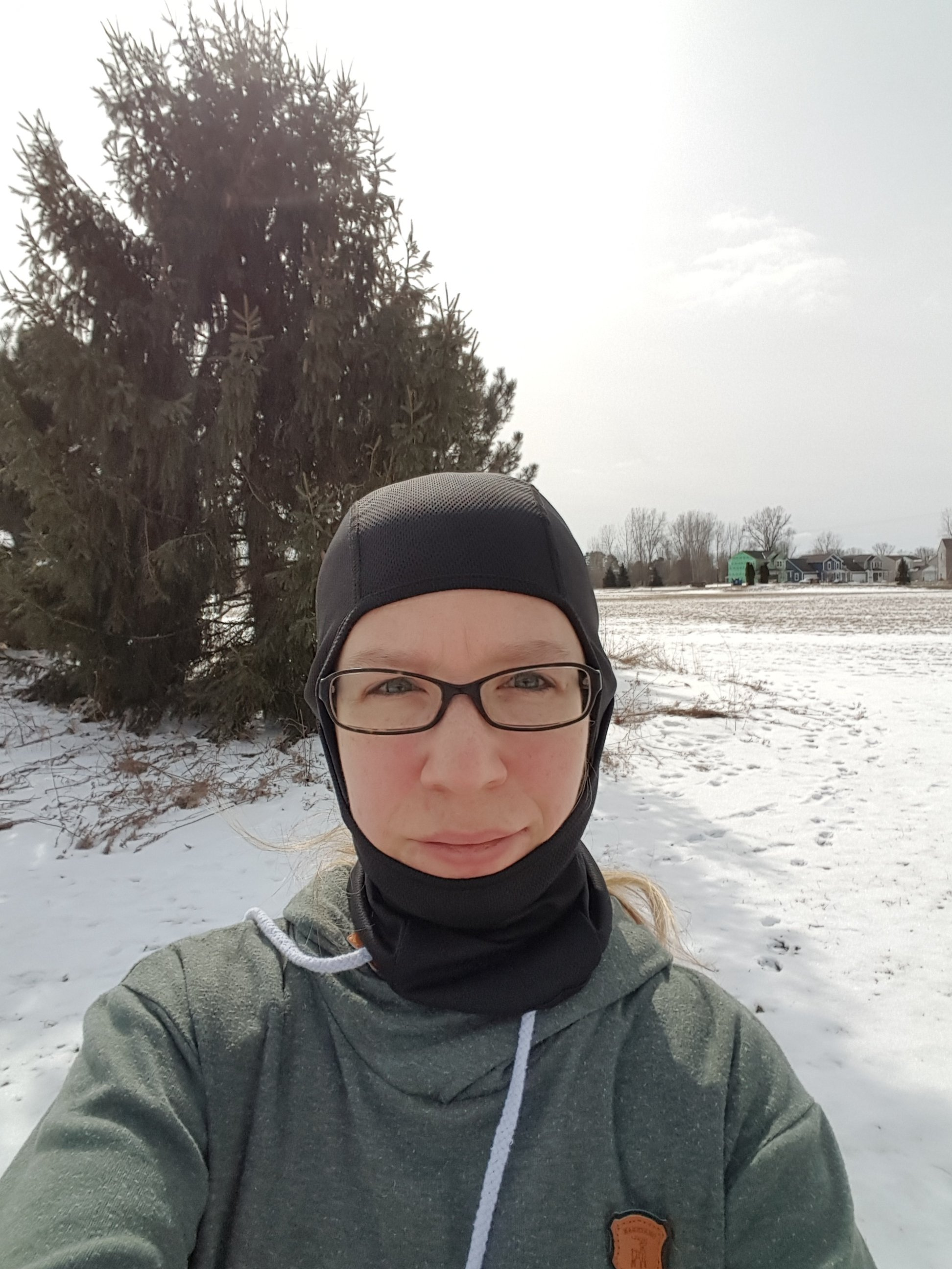 Me, wearing a balaclava on my head, standing in an open field covered in snow.